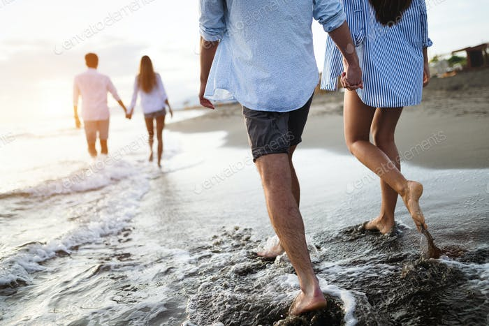Group of friends having fun and walking on the beach at sunset