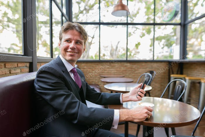 Happy businessman smiling while holding mobile phone and coffee