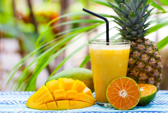 Fresh Tropical Fruit Juice, Smoothie in Glass on Summer Outdoor Background. Copy Space.