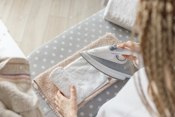 Woman ironing white cloth, top view