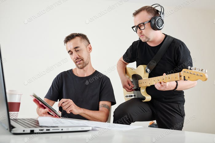 Composer showing song to guitar player