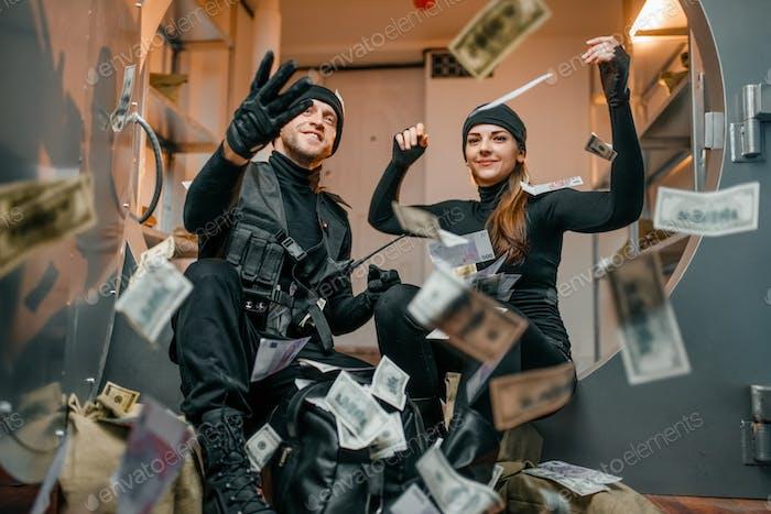 Glückliche Räuber werfen Geld in den Tresor