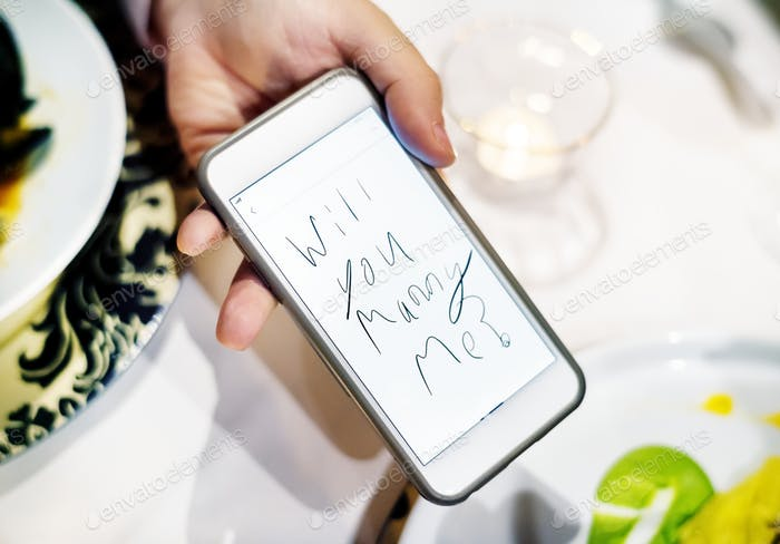 Man proposing woman with mobile phone
