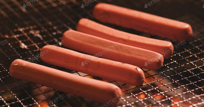 Grilling sausage on BBQ fire