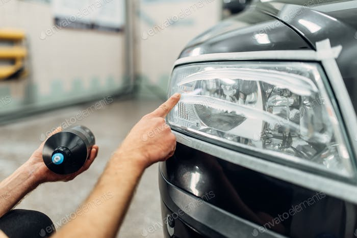 Detailing of headlight, man smears polishing paste