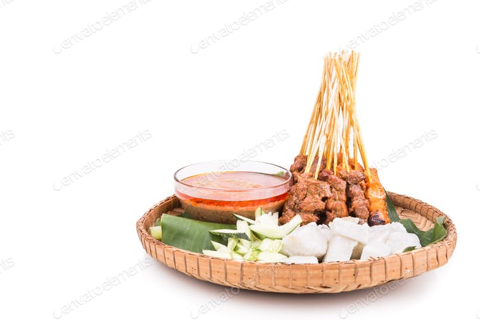 Barbecue satay served on traditional rattan plate with banana le