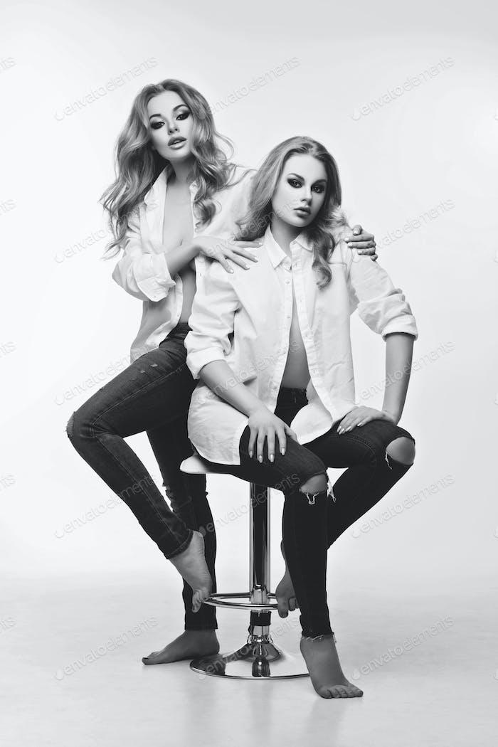 Zwei schöne Mädchen in weißen Hemden und Jeans
