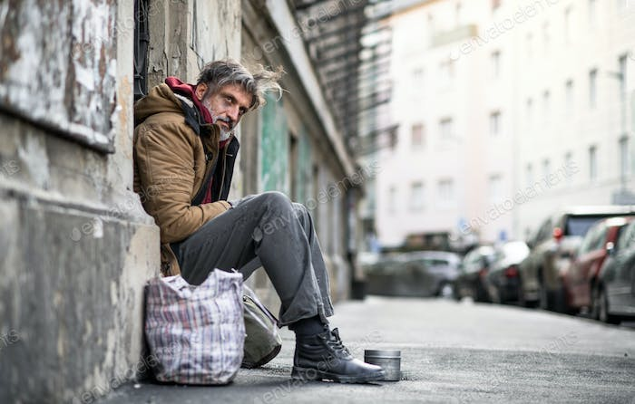 Homeless beggar man sitting outdoors in city, asking for money donation.
