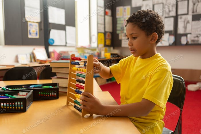 Focused mixed-race schoolboy learning mathematics with abacus in a classroom