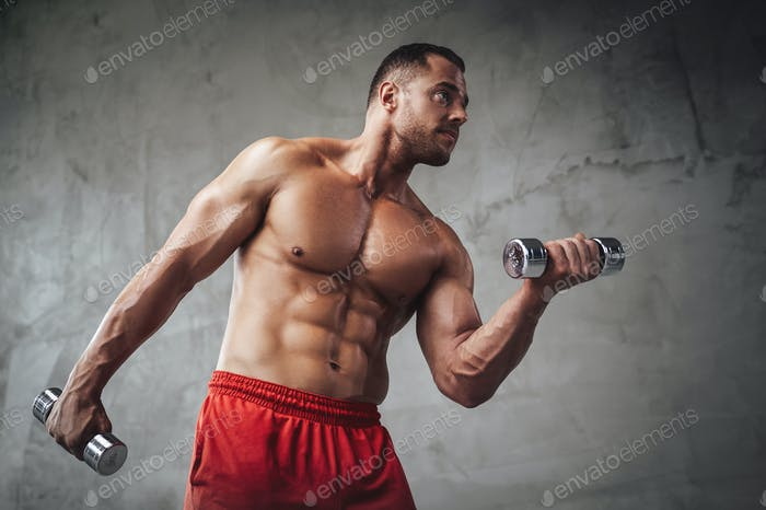 Tanned muscular guy lifting dumbbels in custom background