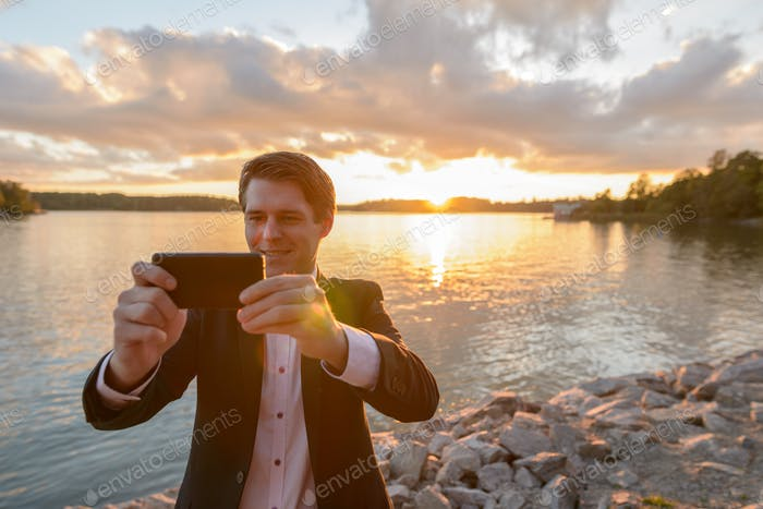 Young happy businessman smiling while taking pictures with mobile phone in beautiful scenic shore