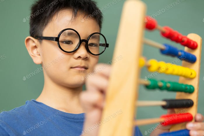 Boy learning math with abacus in a classroom at elementary school