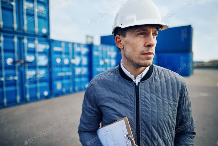 Engineer standing alone on a commercial shipping dock