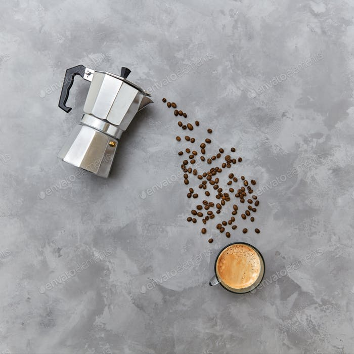 Aromatic coffee beans in the form of a pouring drink from italian metal coffee maker on a gray