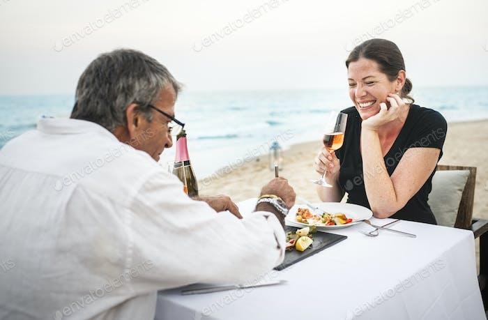 A couple eating dinner on the beach