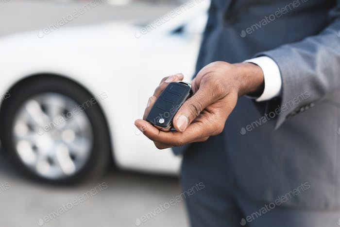 Car rental concept. Young man showing key of his new car