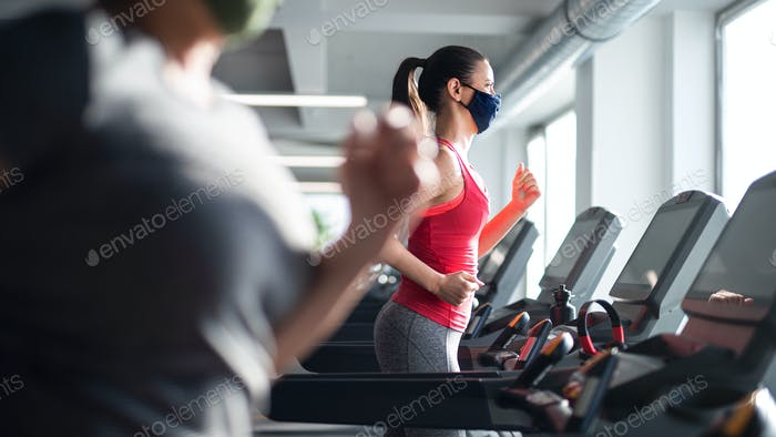 Woman with face mask doing exercise on treadmill in gym, coronavirus concept
