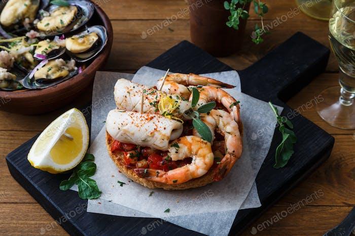 Vorspeise mit würzigen Tomaten Tintenfisch und Garnelen auf Toast