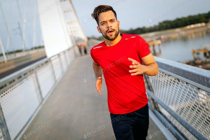 Handsome young man running across the bridge