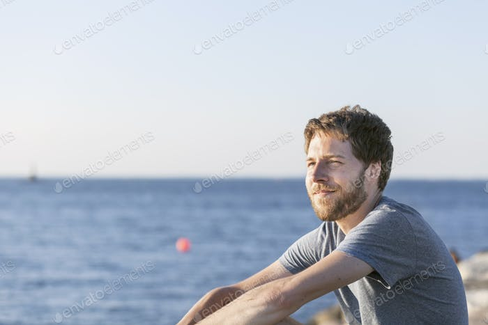 Thoughtful mid adult man looking away at beach