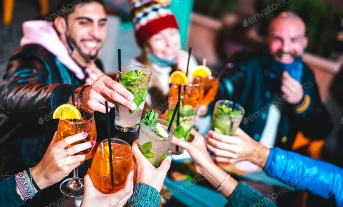 Happy friends toasting drinks at night bar with open face mask