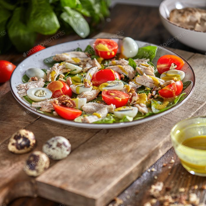 Delicious natural salad with fresly picked green vegetables, chicken meat, quail eggs in a gray
