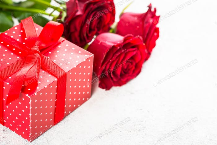 Red roses flower and present box on white.