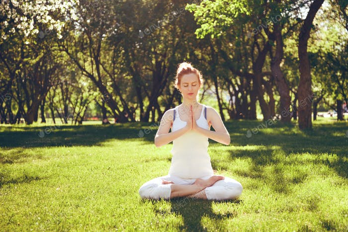 Young red hair woman peacefully meditating in park