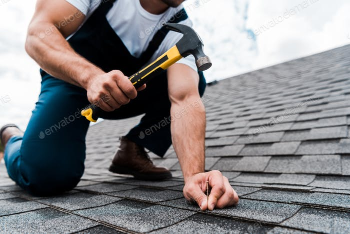 cropped view of handyman in uniform holding hammer while repairing roof