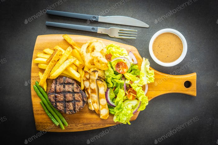 Grilled beef meat steak with french fries sauce and fresh vegeta