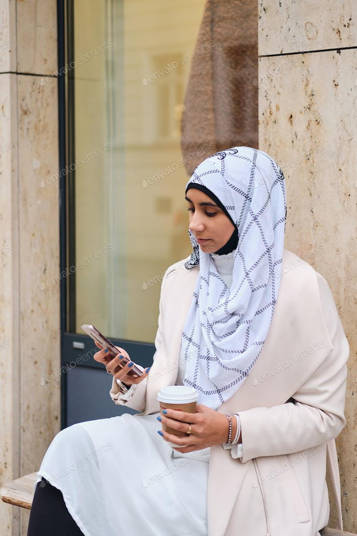 Attractive Arabic woman in hijab using smartphone while sitting on city street with coffee to go