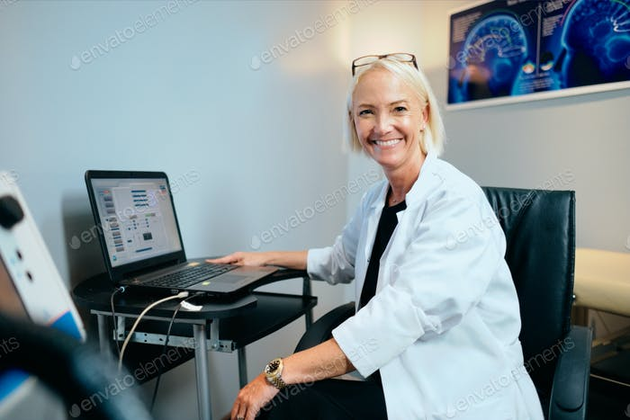 Portrait Female Doctor Working In Hospital Office With Computer Smiling