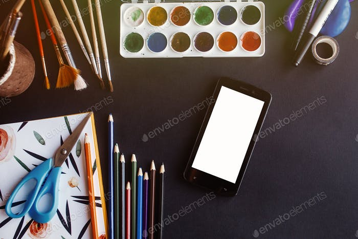 smartphone cell with empty white screen and colorful pencils paints brushes scissors