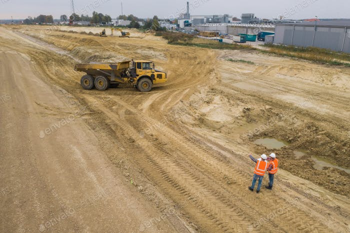 Top view of two road construction workers in the middle on the field