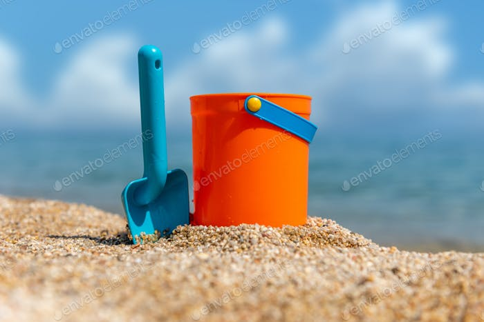 Children's beach toys - buckets and spade on sand in a sunny day