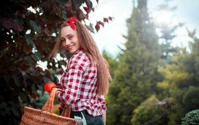 Young gardener woman going to gardening in her garden with tools