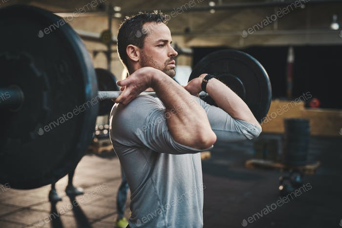 Man pulling up large barbell in fitness class