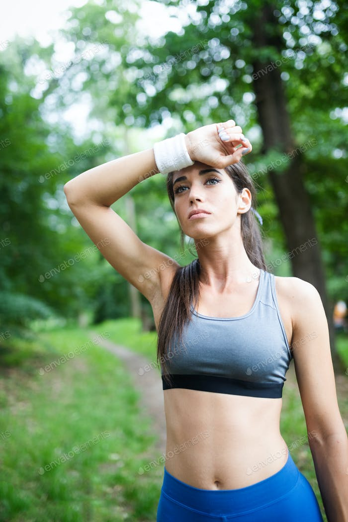 Portrait of athletic woman resting after running in nature
