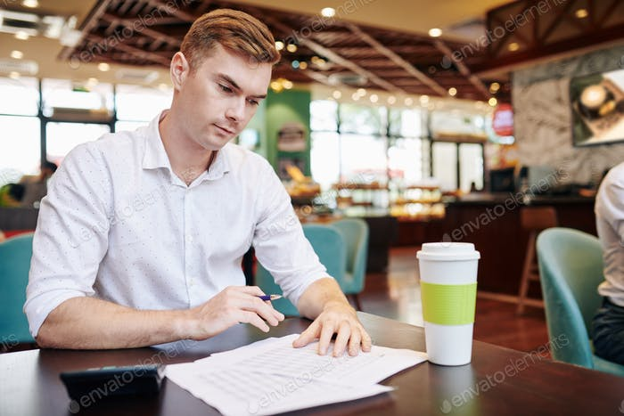 Young businessman checking report