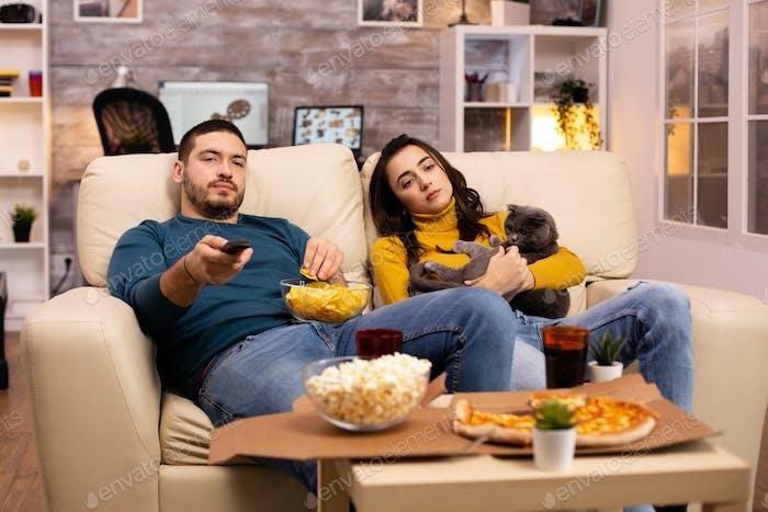Schönes junges Paar Fernsehen und Essen Fast Food zum Mitnehmen