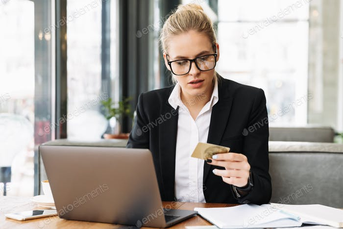 Concentrated blonde business woman sitting by the table in cafe