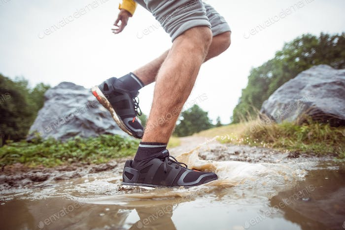 Man splashing in muddy puddles in the countryside
