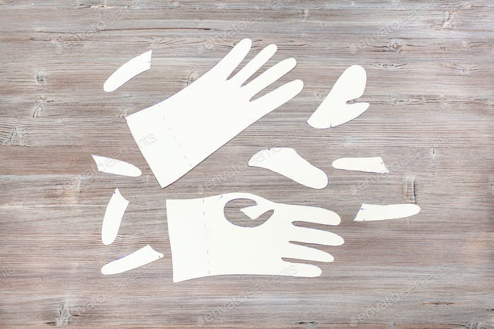paper templates of gloves on wooden table