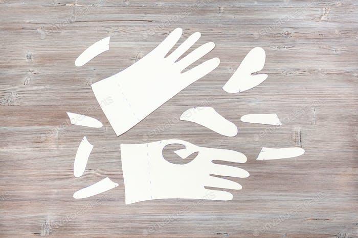 PapierVorlagen von Handschuhen auf Holztisch
