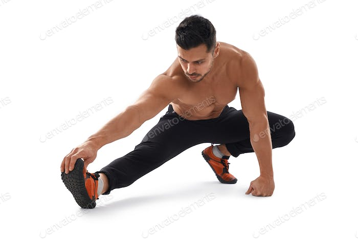 Shirtless bodybuilder stretching on floor