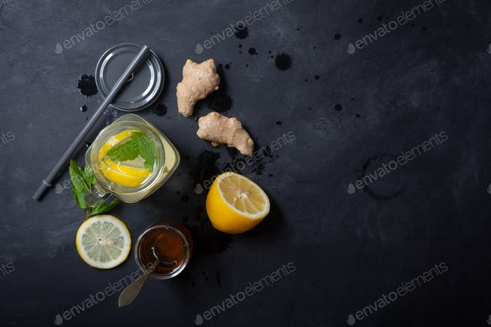 Ginger Water in Glass jar With Lemon and Honey on a Black Background With Copy Space