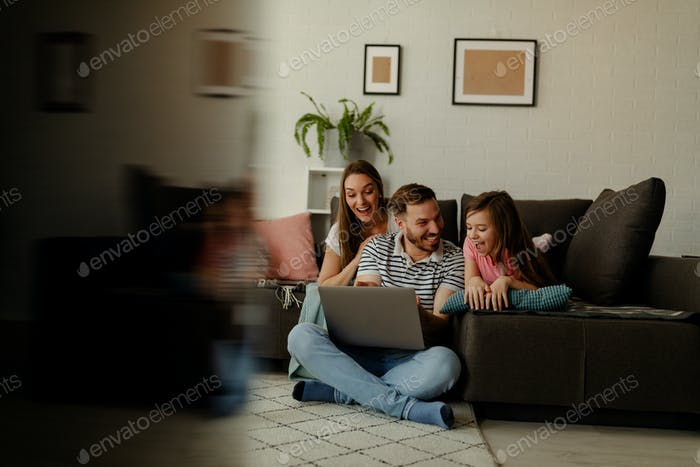 A picture of a happy family. A young family spends time at home playing video games on a laptop.
