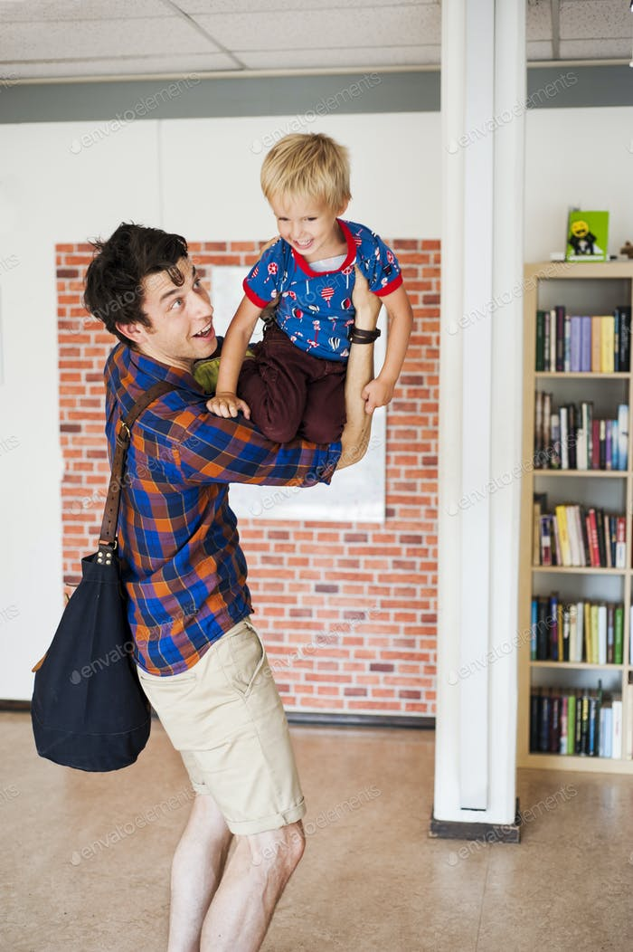 Playful father lifting son at primary school