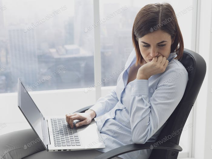 Pensive businesswoman working with her laptop