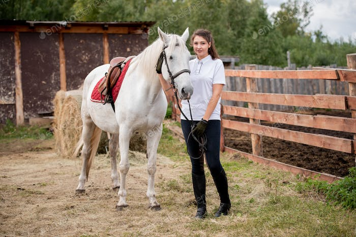 Young active woman chilling out with white purebred racehorse